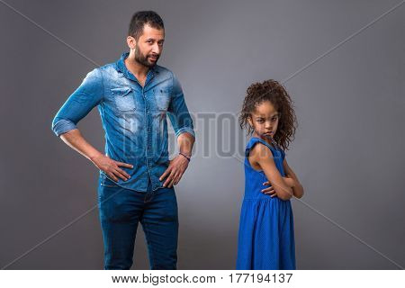 A young black man arguing with his teenage daughter who is turning her back to him