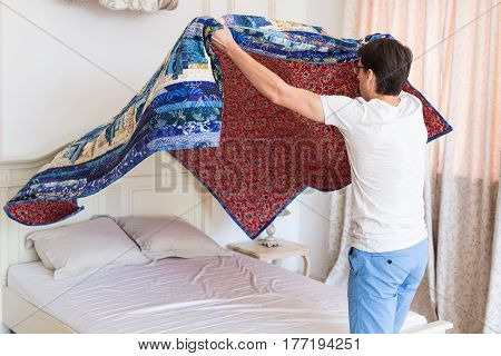 handsome young man making bed a color patchwork quilt in the white interior. scrappy blanket on the bed closeup. Handmade.