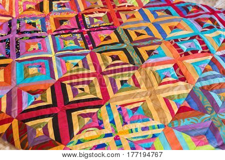 Part of symmetric geometry pattern color patchwork quilt as background. Colorful Scrappy blanket. Handmade. Sewing concept.