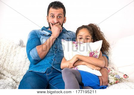 A young black father siting together with his daughter on the couch who is hiding behind a pillow and feeling scared