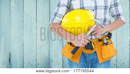 Digital composite of Carpenter torso with hammer against blue wood panel