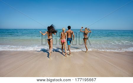 Rear view shot of group of friends running into sea water. Active people having fun on the beach on vacation. Tourists going for swim.