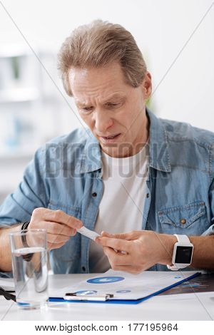 I am shocked. Attentive man wearing jeans shirt, wrinkling his forehead while looking at piece of paper