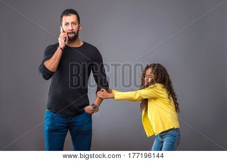 A black father talking on his phone while his young daughter pulling his arm