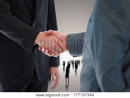 Digital composite of Handshake in front of silhouette business people