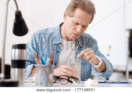 Want to be healthy. Attentive male wearing jeans shirt, pressing his lips while looking at glass