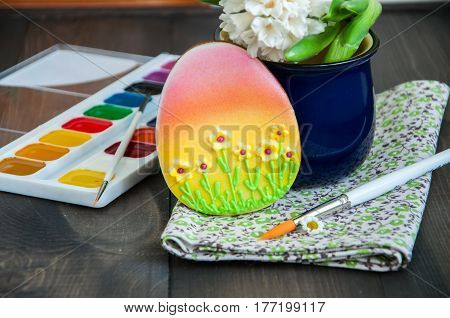 Decorated Easter Egg Cookies Chamomile Hyacinth Paints and Brushes on a wooden background. Easter concept.