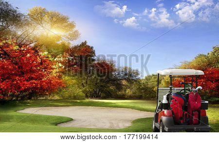 Autumn Foliage at the Golf Course - The sun shines on a putting green and lake at a golf course in Autumn.