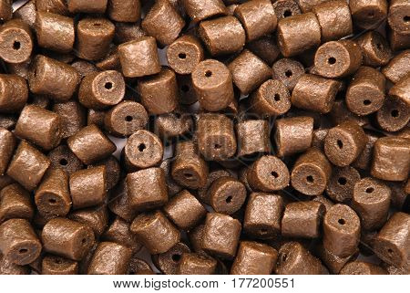 Brown pre-drilled halibut pellets for carp fishing background