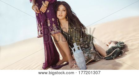 Women traveling in desert. Dehydration, overheating, thirst and heat stroke concept image with two sisters outdoors in the nature. Arabian girls lost in dunes during journey.
