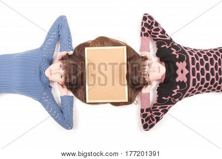 Portrait of two twins sisters with long hair and cork board on the hair top view on white background