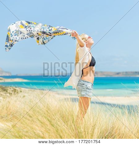 Relaxed woman, arms raised, holding colorful scarf, enjoying sun, freedom and life at beautiful beach. Young lady feeling free, relaxed and happy. Concept of vacations, freedom, joy and well being.