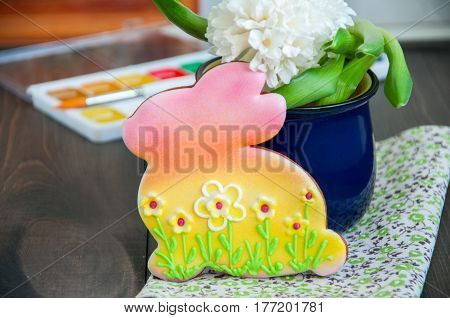 Decorated Easter Bunny Cookies Hyacinth in a jar Paints and Brushes on a wooden background. Easter concept.
