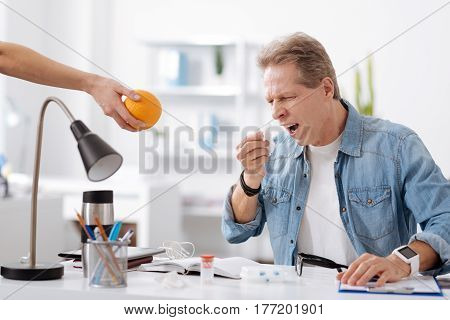Take vitamins. Frustrated man wearing casual clothes, keeping his mouth wide opened looking at orange