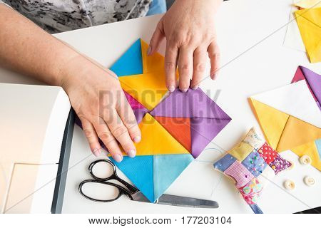 female hands holding geometrical colored fabric pieces for patchwork quilt. fashion designer creates new collection of clothes. flat lay. top view.
