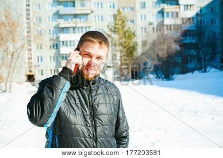 Telephone Calls Men. The Guy Is Talking On Cell Phone In Street In Winter, Dressed In Warm Clothes,