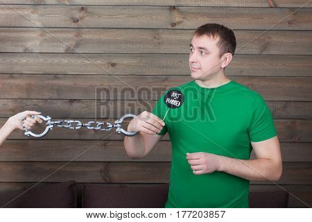Young handcuffed man holding funny icon on a stick