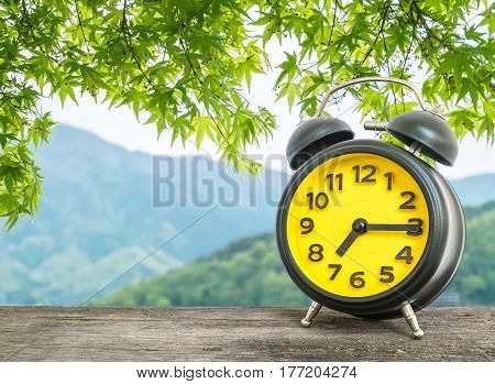 Closeup black and yellow alarm clock for decorate show a quarter past seven or 7:15 a.m. on blurred leaves and mountain view background