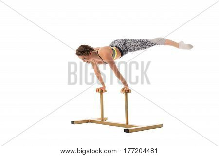 Pretty woman in top and leggings doing exercises on special stand in studio isolated shot