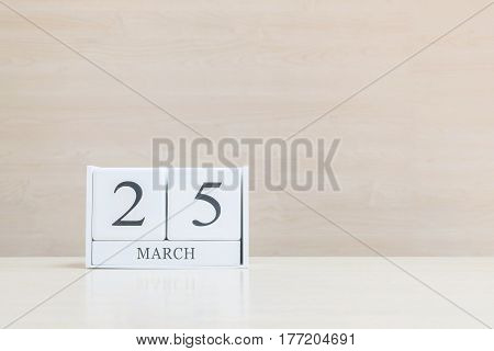 Closeup surface white wooden calendar with black 25 march word on blurred brown wood desk and wood wall textured background with copy space selective focus at the calendar