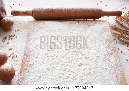 Baking class or recipe concept on white background, sprinkled wheat flour on wooden board on table. Cooking dough or pastry.