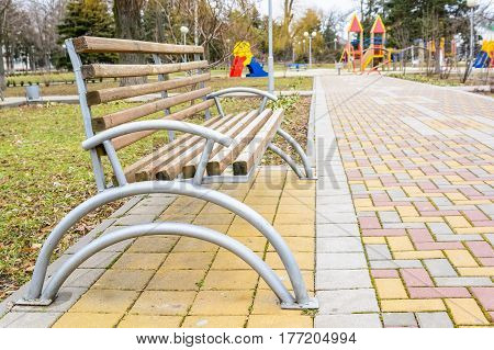 New empty wooden and metal bench in park