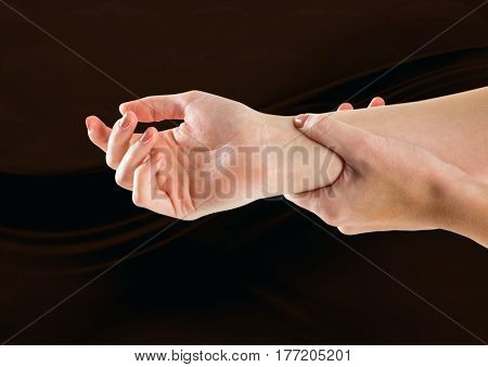 Digital composite of woman hands restraining against dark background