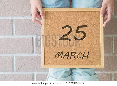 Closeup calendar at the cork board in hand of asian woman in front of her legs with 25 march word on brick wall textured background