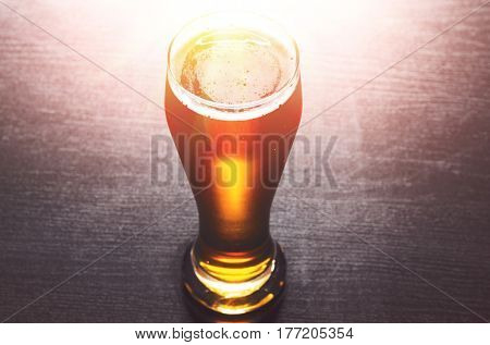 glass of fresh lager beer on black table
