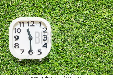 Closeup white clock for decorate show a half past eleven or 11:30 a.m. on green artificial grass floor textured background with copy space