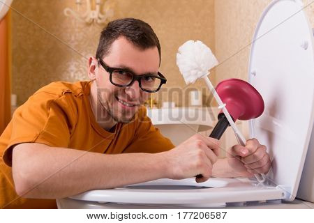 Man in glasses cleaning the toilet bowl