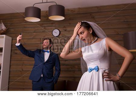 Dissatisfied bride and groom making selfie