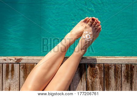 Girl at tropical swimming pool with sunscreen
