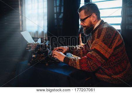 Bearded writer in glasses typing on a typewriter