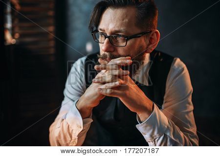 Serious brooding bearded man in glasses
