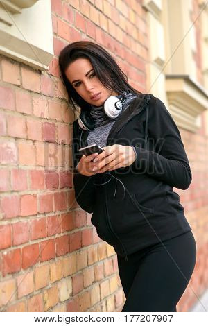 A beautiful young woman wearing sportswear and leaning to a brick wall while using her phone