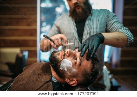 Barber shaves beard of the client at barbershop