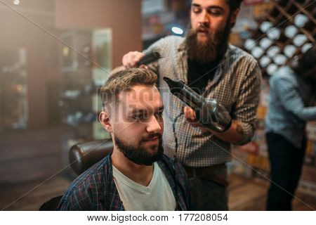 Barber washes the hair of a client man