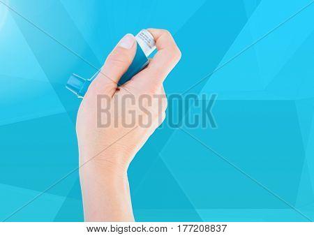 Digital composite of Hand holding Ashtma Inhaler against blue background