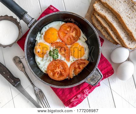 Yummy eggs overeasy in a frying pan, eggs and bread on the side, topview