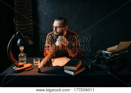 Bearded writer in glasses sitting at the table