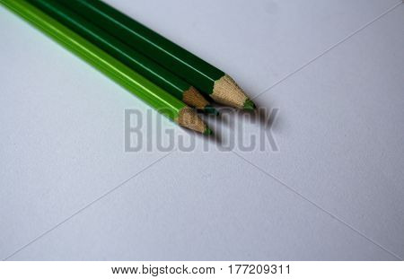 a green color pencils and white paper