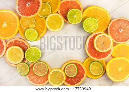 A vibrant frame made up of juicy citrus fruits, on a white marble texture, with copy space. Grapefruit, lime, lemon, and orange slices