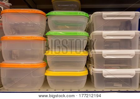 Plastic food containers with colorful lids on shelf in shop