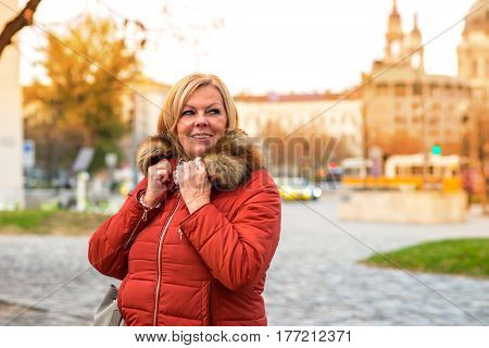 A nice middle age woman standing on the street and grabbing the neck of her winter jacket