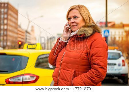 A nice middle age woman standing and waiting for her taxi while talking on the phone