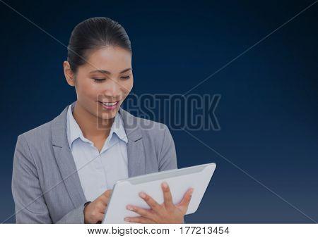 Digital composite of Businesswoman using tablet against a dark blue background