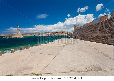 Chania Crete - 26 June 2016: People are walking on the embankment in the Old Town of Chania and Chania Lighthouse on the summer sunny day. Embankmentis located near the Old Town of Chania and it is favorite place for tourists who are visiting and walking