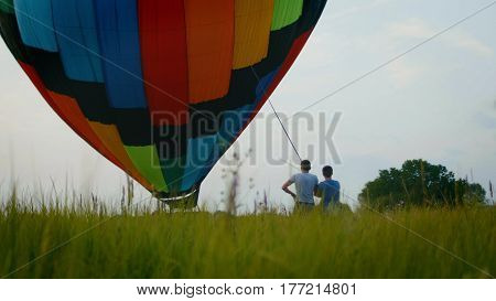 Colorful hot air balloon on summer field at sunset, wide angle