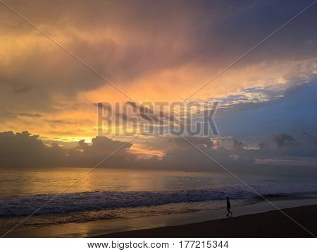 In the sky a beautiful sunset with clouds over the ocean and a silhouette of a man